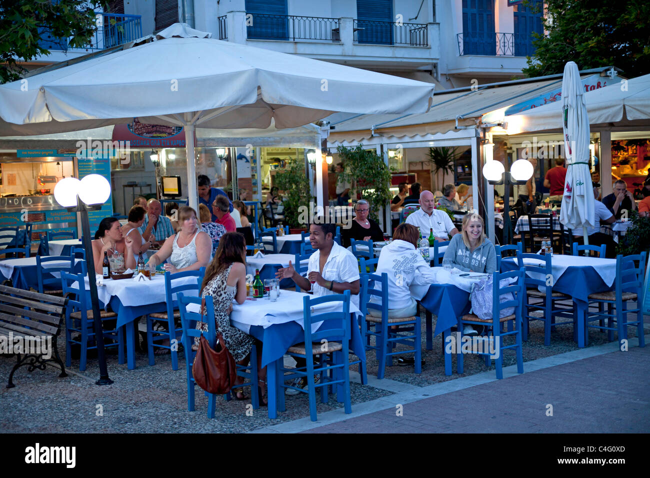 busy restaurant at the old harbour of Skiathos Town, Skiathos Island, Northern Sporades, Greece  - Stock Image