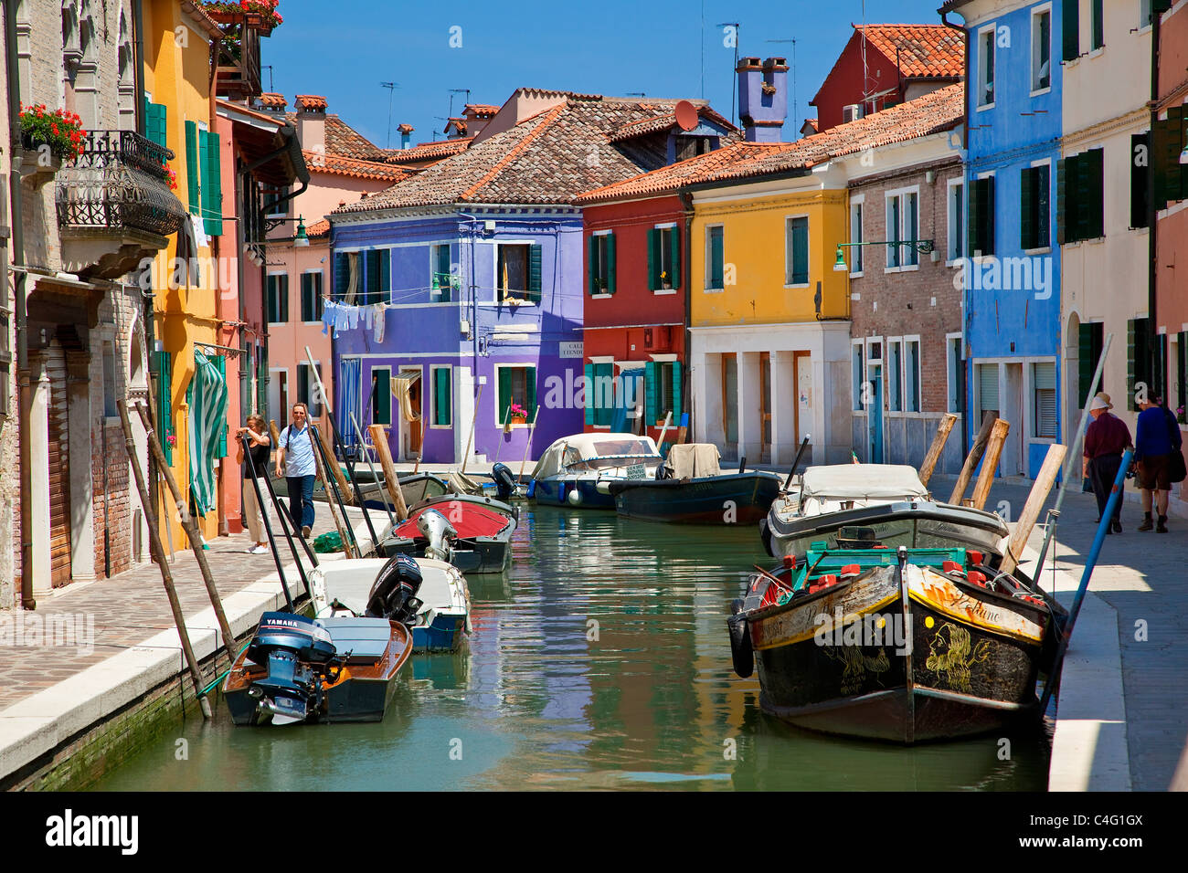 Venice, Burano, Colorful Boats and Homes Lining Canal - Stock Image
