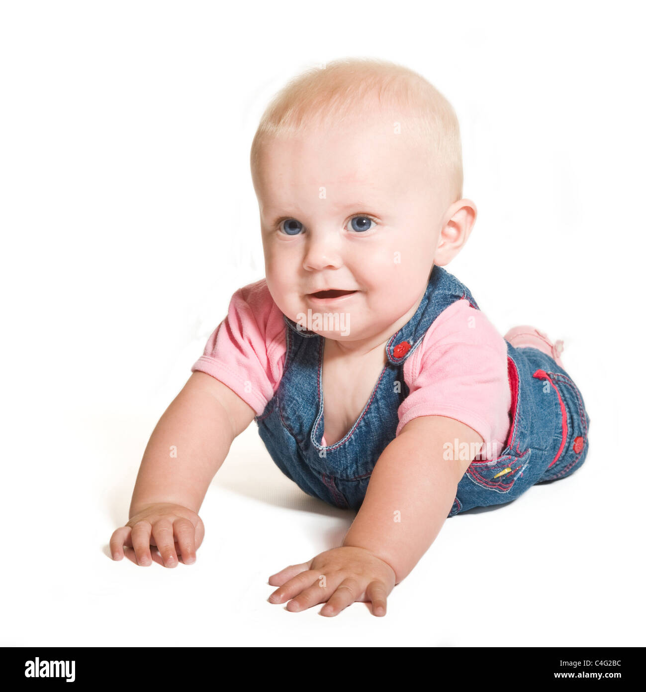A cute 1 year old baby girl with blue eyes wearing denim and pink smiling  against a pure white (255) background.