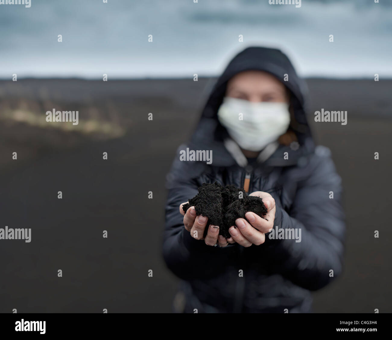 Woman holding new ash from recent Grimsvotn volcanic eruption, Iceland - Stock Image