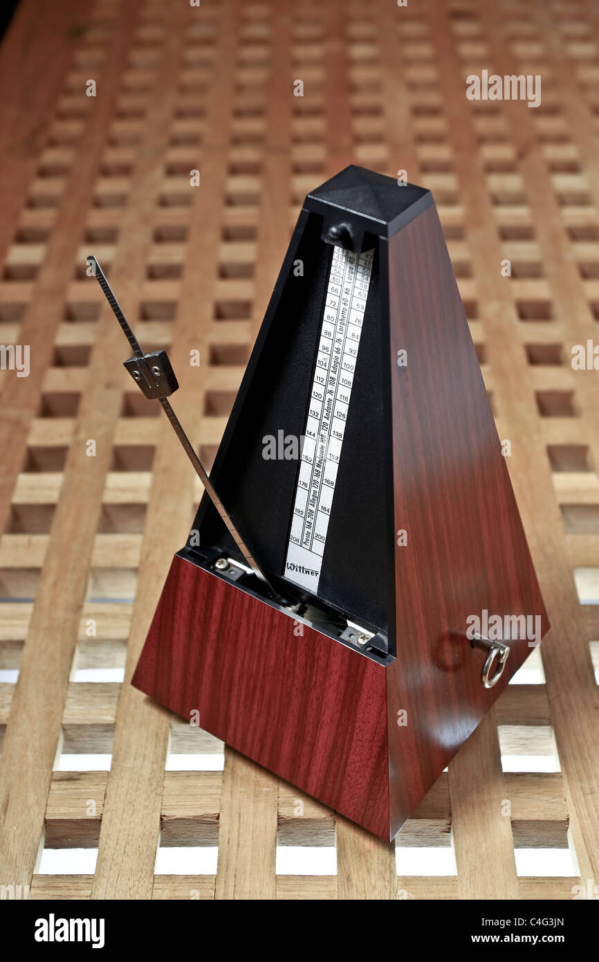 A Metronome on a wood top - Stock Image