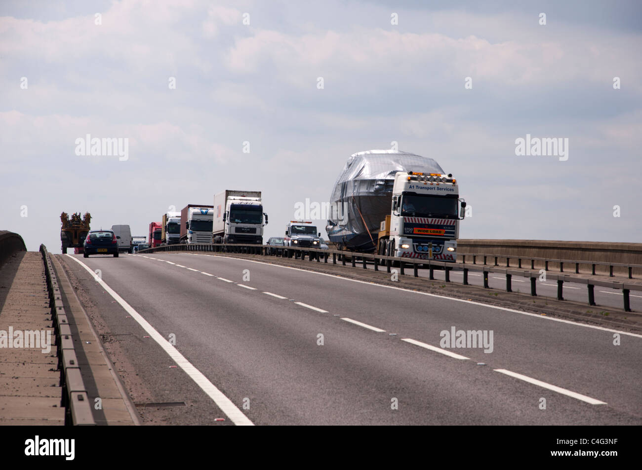 Wide load lorry carrying boat - Stock Image