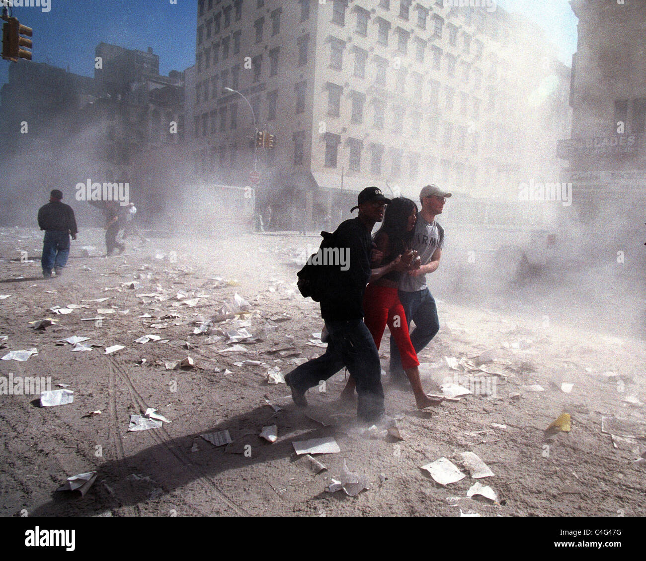 People attempt to escape the debris and concrete dust in the air on September 11, 2001 after WTC terrorist attack - Stock Image