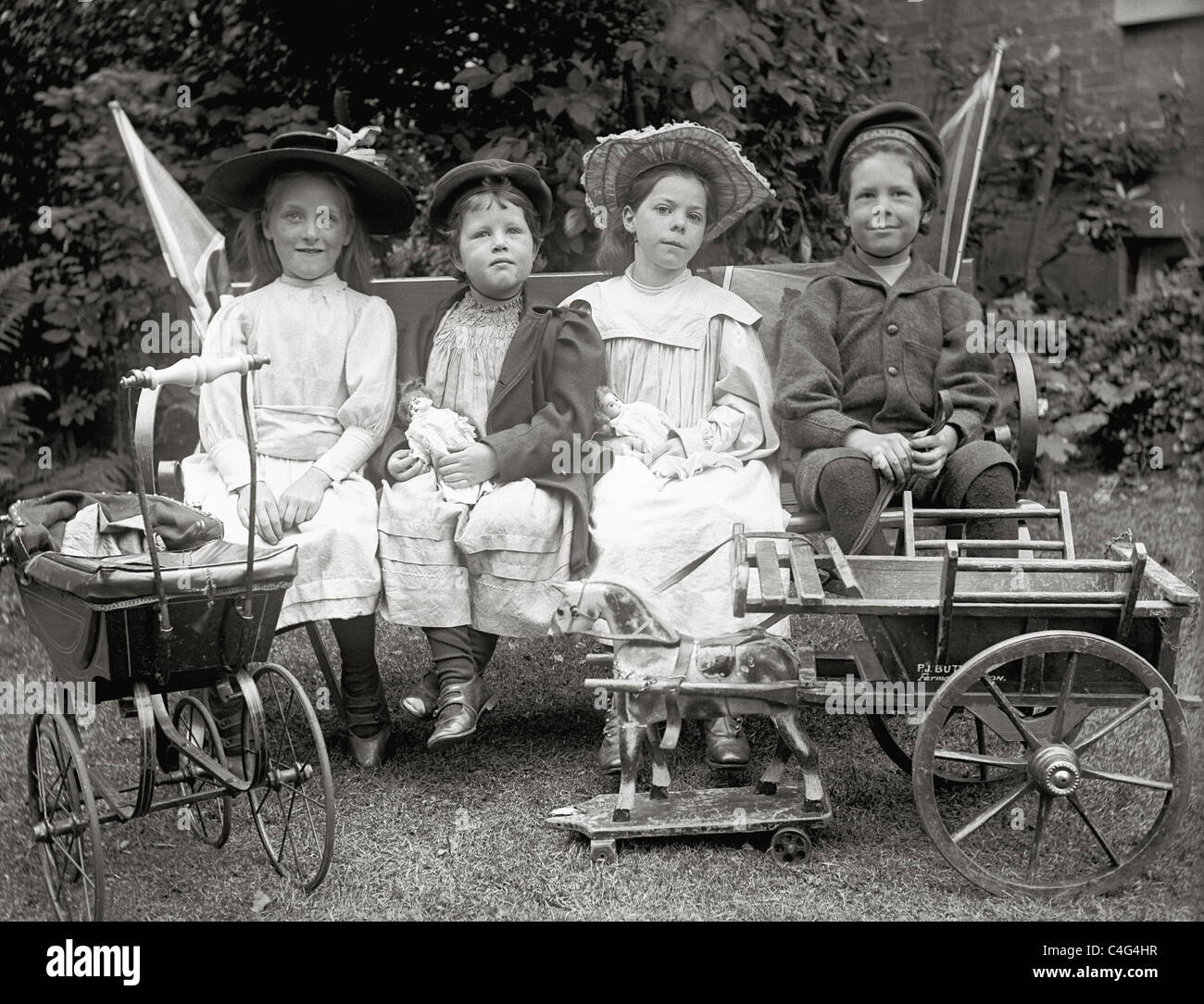 Victorian or Edwardian children sitting in garden with their toys - Stock Image