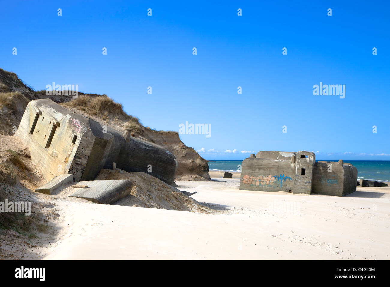 Old world ware II air-raid shelters on the beach in Loekken Denmark - Stock Image