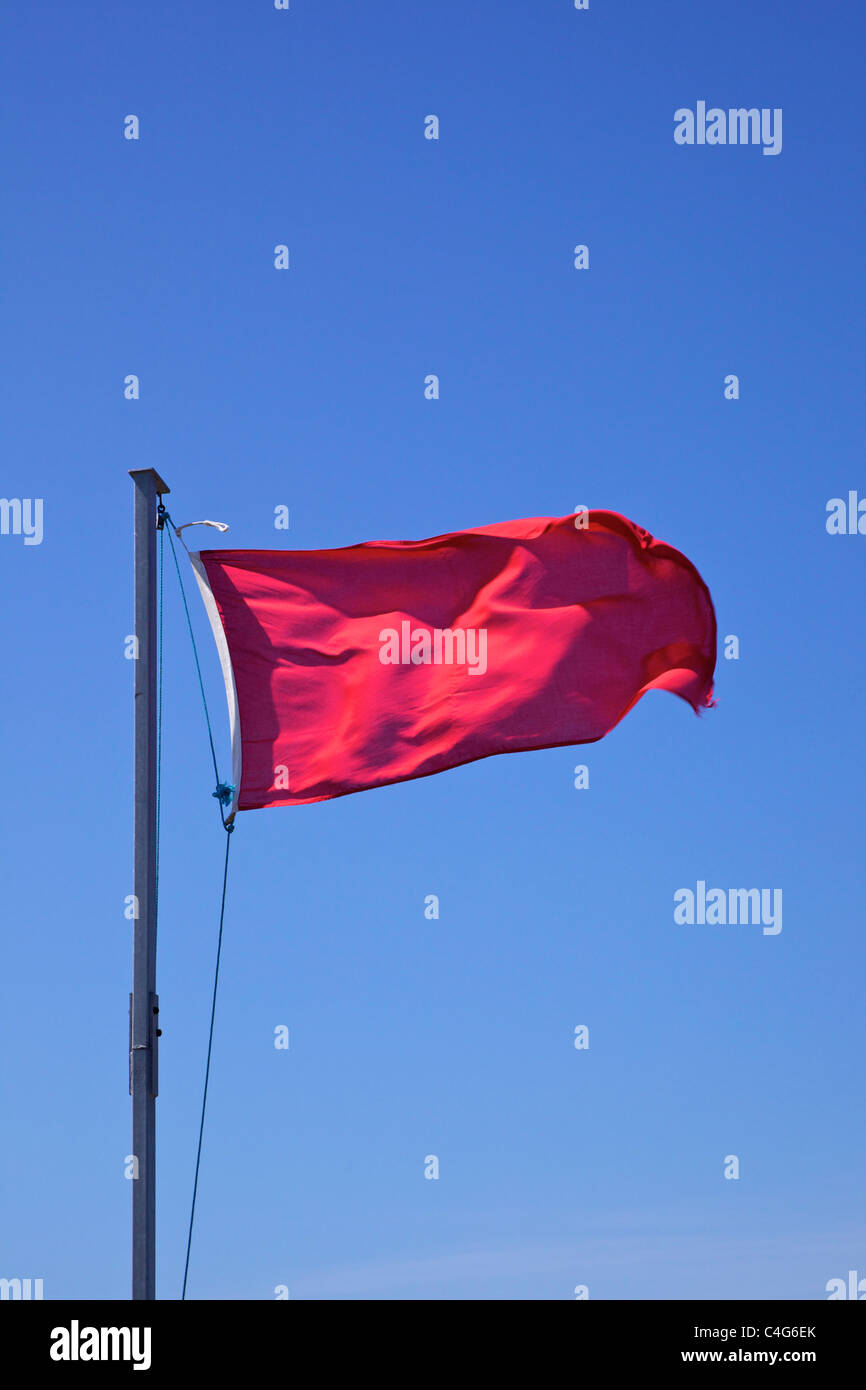Red flag waving against blue sky - Stock Image