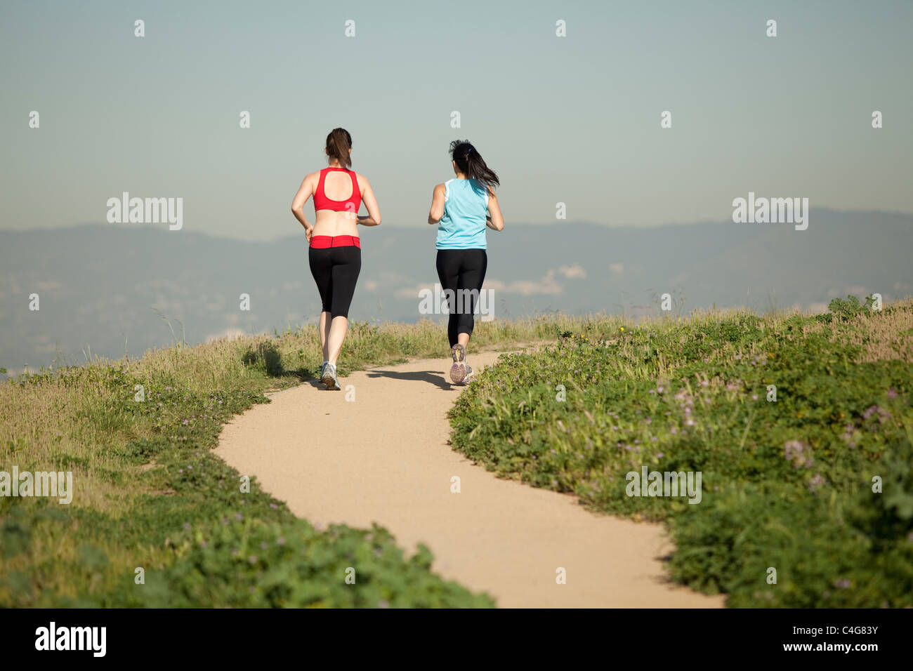 two athletic females, in workout clothes,  running on a dirt path through nature in the daytime - Stock Image
