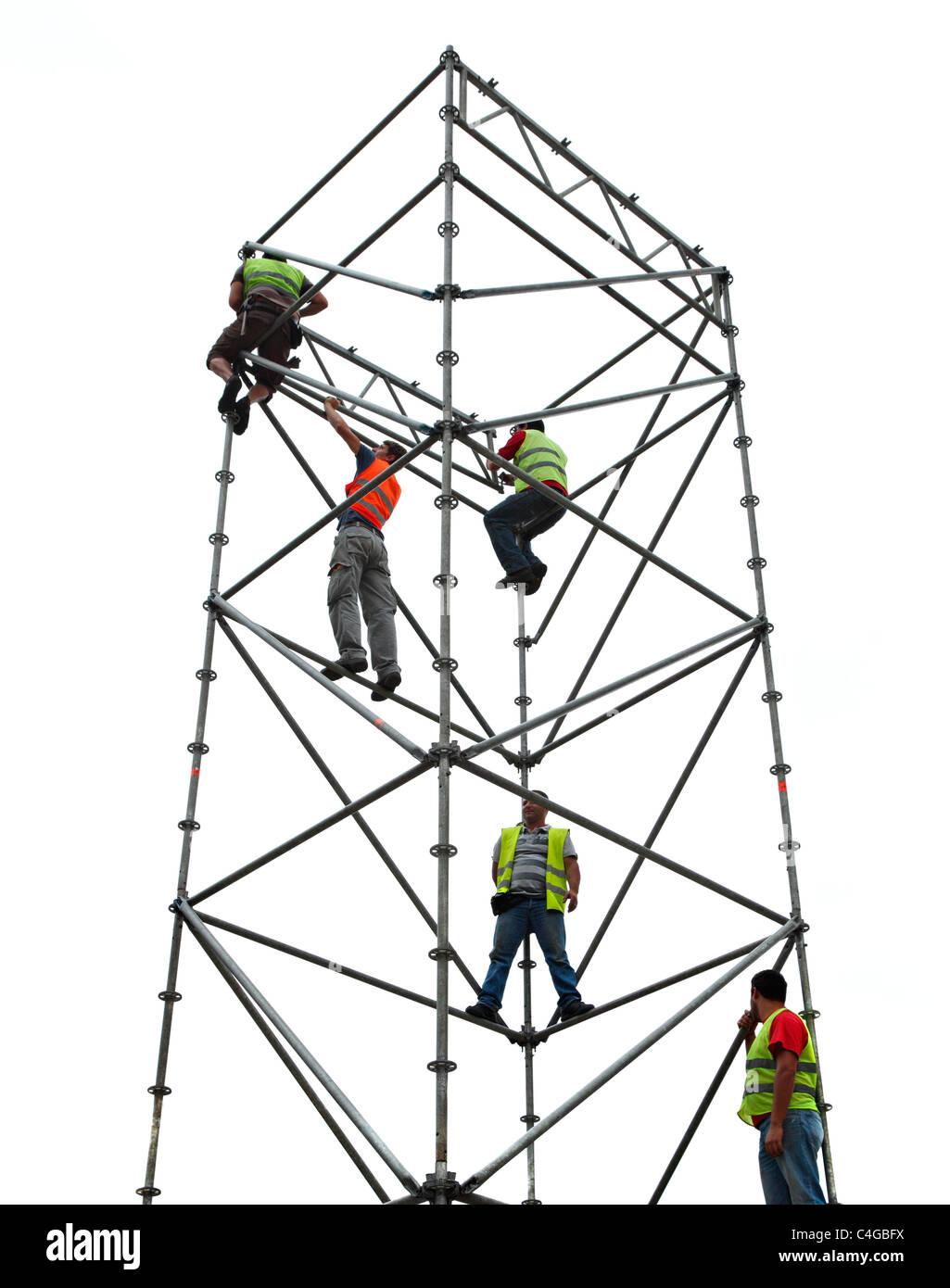 Team of men erecting tower scaffolding. - Stock Image