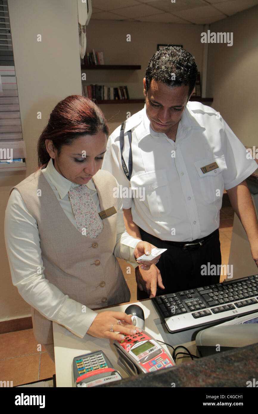Santo Domingo Dominican Republic Ciudad Colonia Mercure Comercial hotel front desk hospitality Hispanic man woman - Stock Image