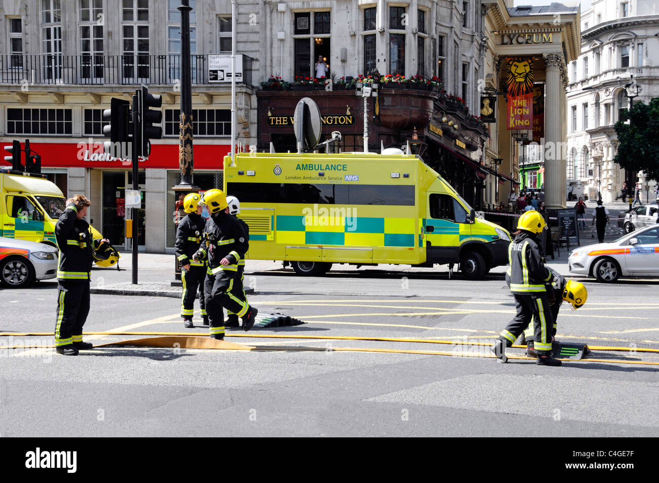 Firemen laying out hoses to fight major fire at Aldwych London ambulance control vehicle beyond - Stock Image
