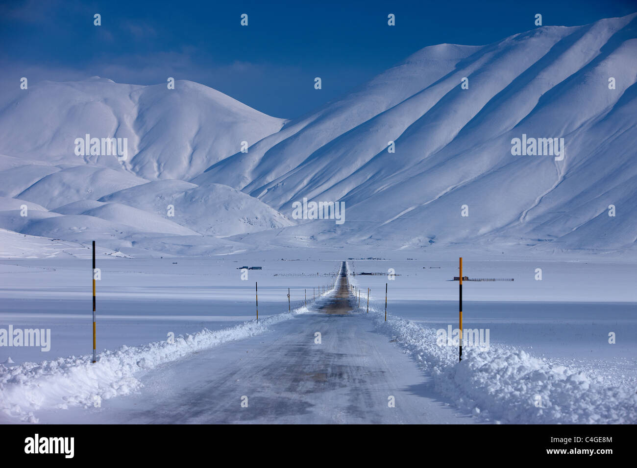 the road across the Piano Grande in winter, Monti Sibillini National Park, Umbria, Italy - Stock Image