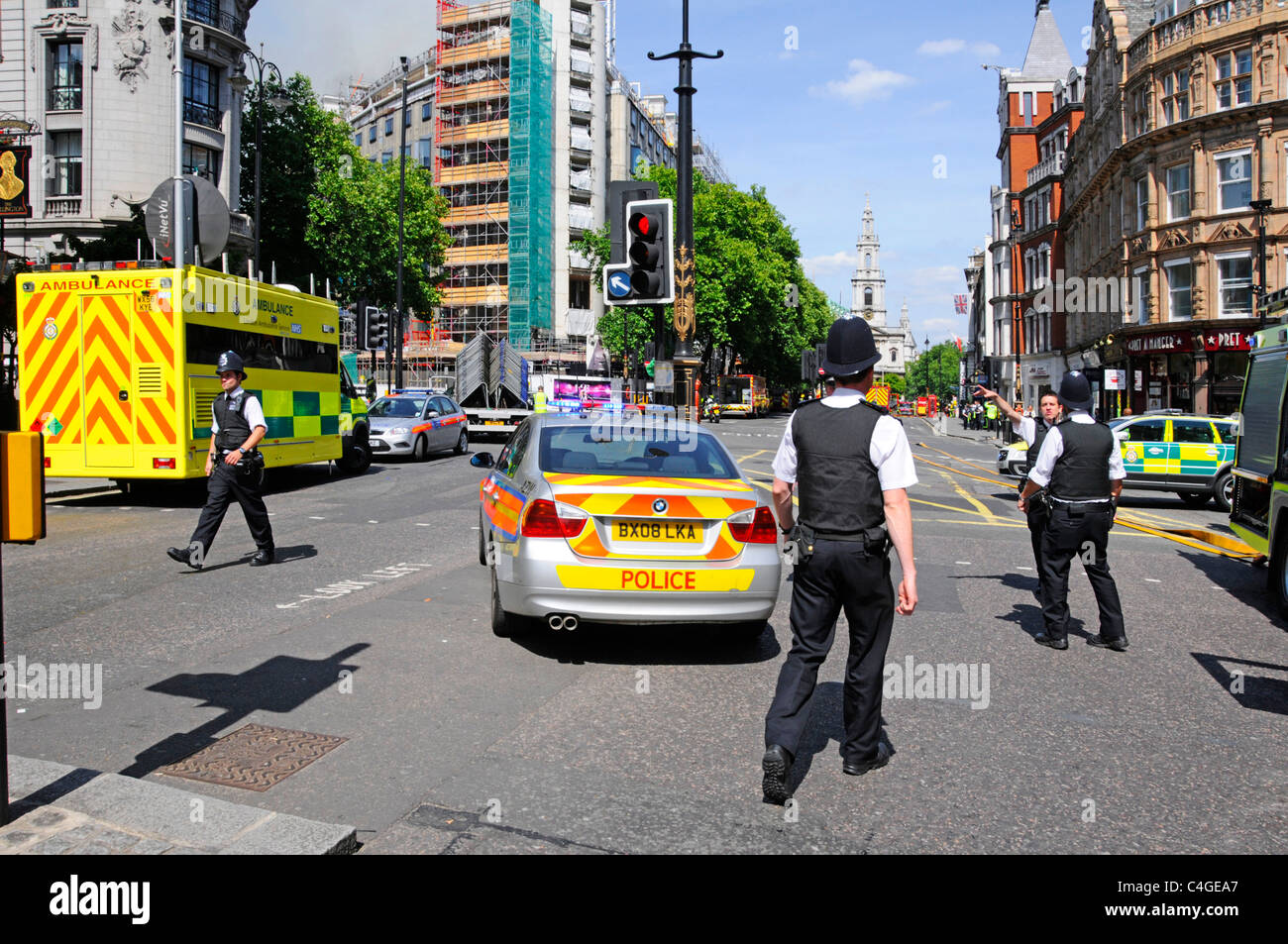 Police vehicles in The Strand with major fire incident in Aldwych beyond - Stock Image