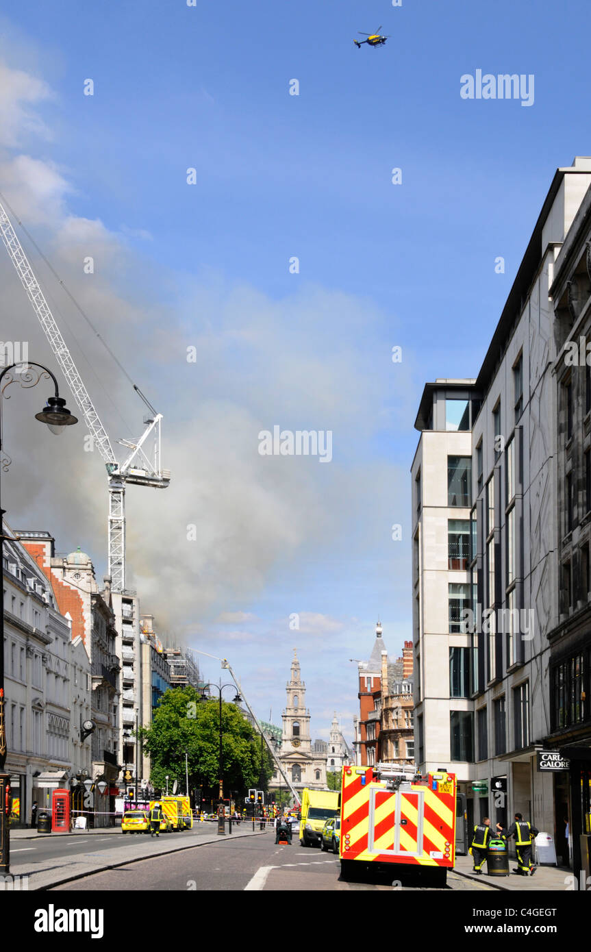 Police helicopter hovers above major fire at Marconi House at Aldwych with Strand closed to traffic - Stock Image