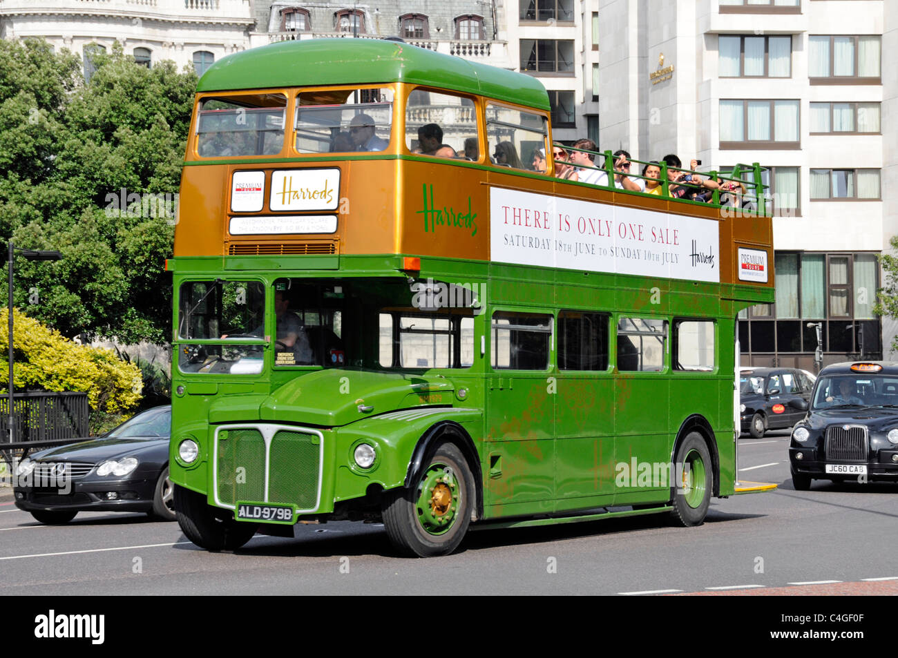 Premium Tours open top Routemaster tour bus in Harrods store livery and Sale advert - Stock Image