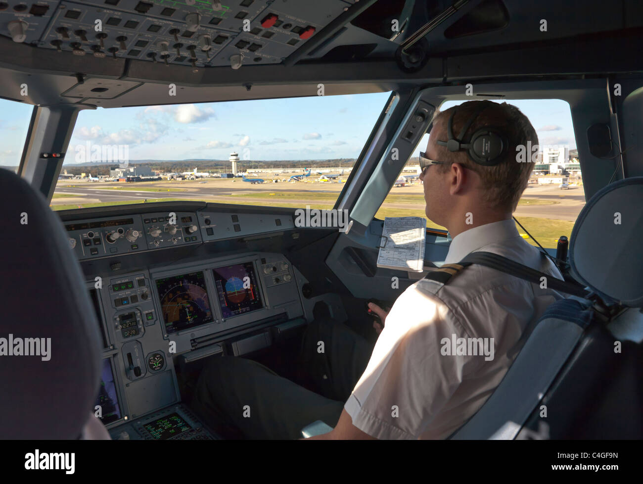 Pilot at controls of an Airbus A320 passenger aircraft - Stock Image