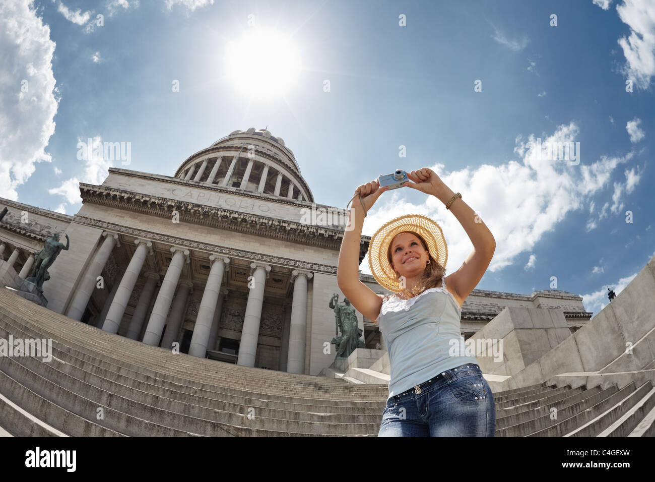 young adult blonde woman taking picture with digital camera in Havana, Cuba. Horizontal shape, waist up, low angle - Stock Image