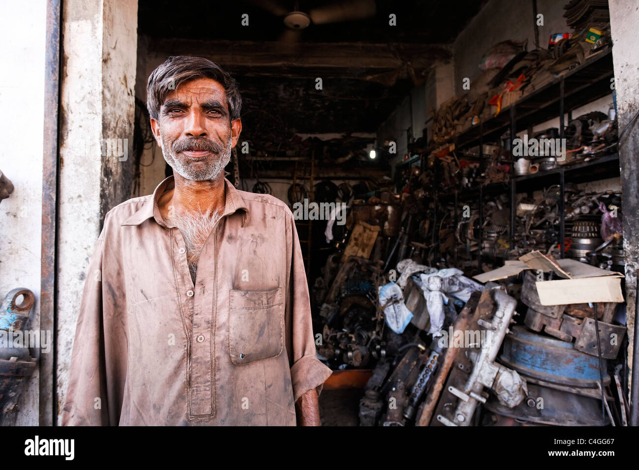 Pakistan - Punjab - Rawalpindi - mechanic and his workshop in the truck repair district - Stock Image