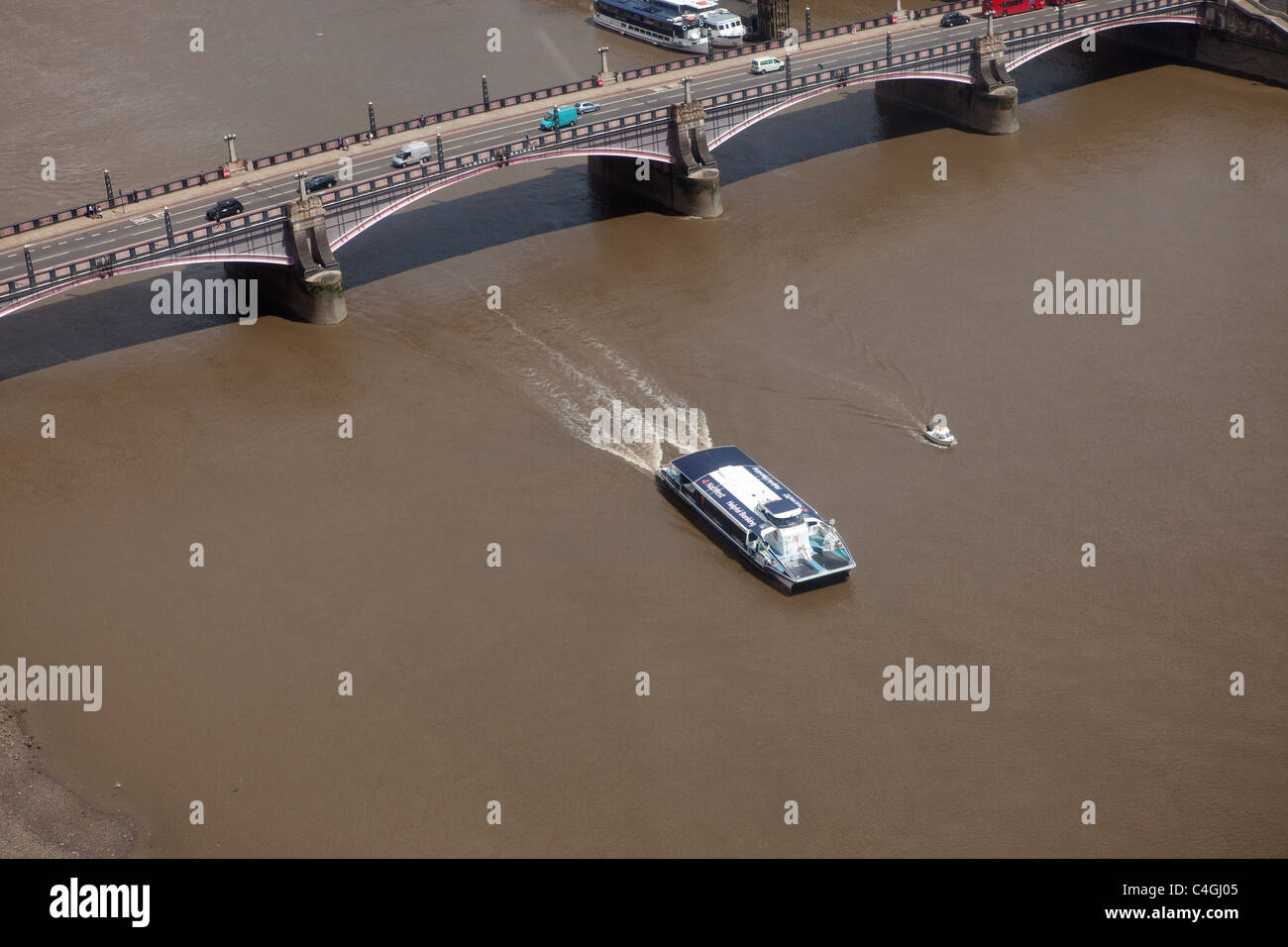 A passenger boat passes under Westminster Bridge on Thames in London - Stock Image