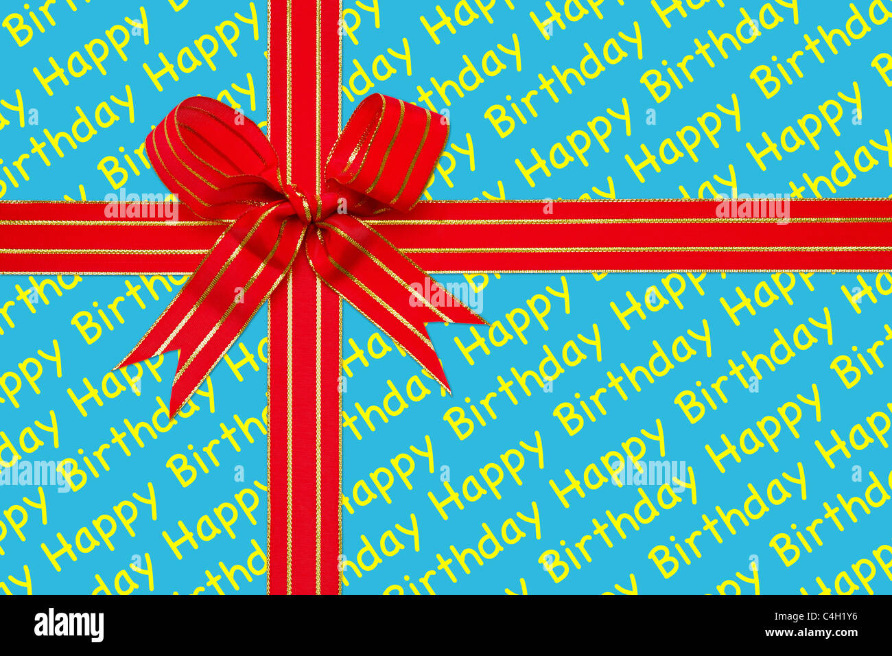Photo of a red and gold ribbon tied in a bow on Happy Birthday wrapping paper. - Stock Image