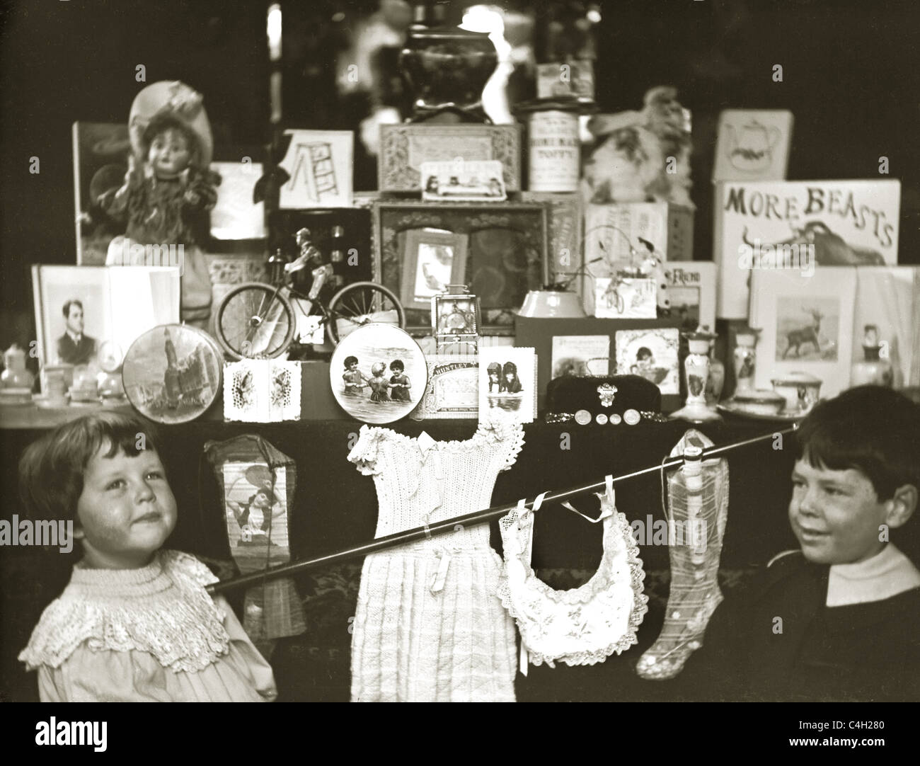 Original photograph of  Edwardian or Victorian children looking in the shop window / shop front of a toy shop, retro - Stock Image