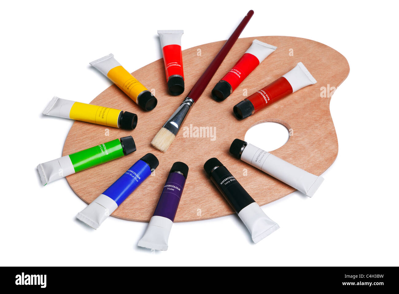 Photo of a wooden artists palette with tubes of watercolour paint and a brush, isolated on white with clipping path. - Stock Image
