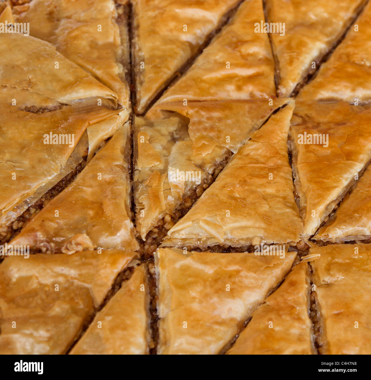 Triangular shapes of Baklava, a pastry made of ingredients including phyllo leaves, nuts, and honey. Stock Photo