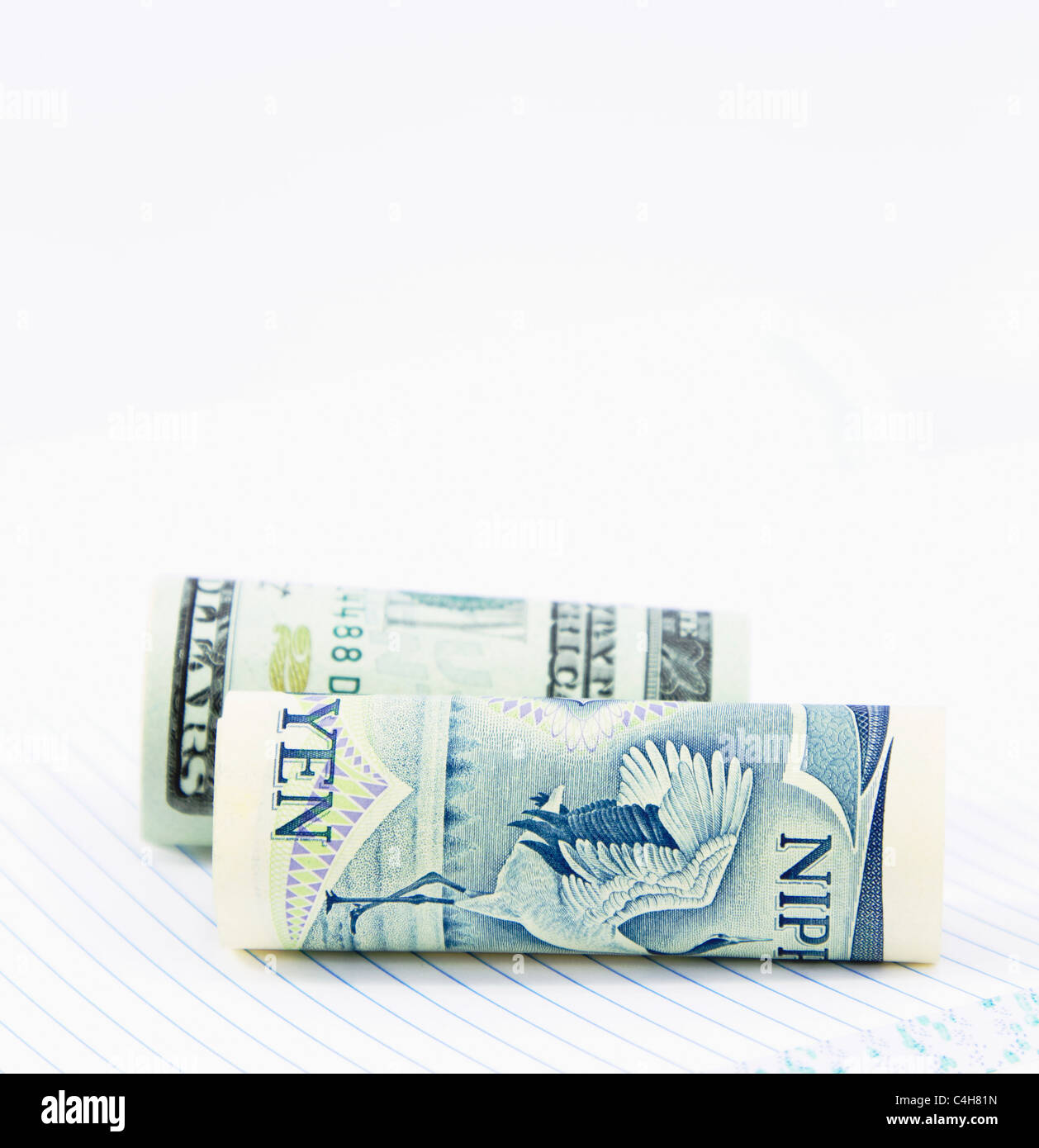 On a notebook with lined pages, two currencies, the dollar and yen, are positioned together in close up image. - Stock Image