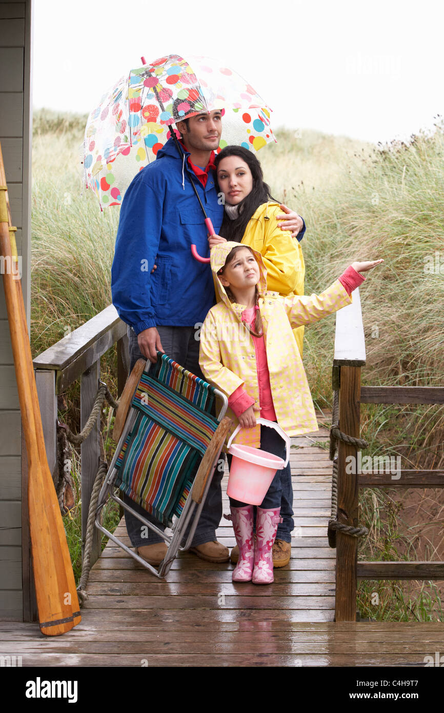 Family on beach with umbrella - Stock Image