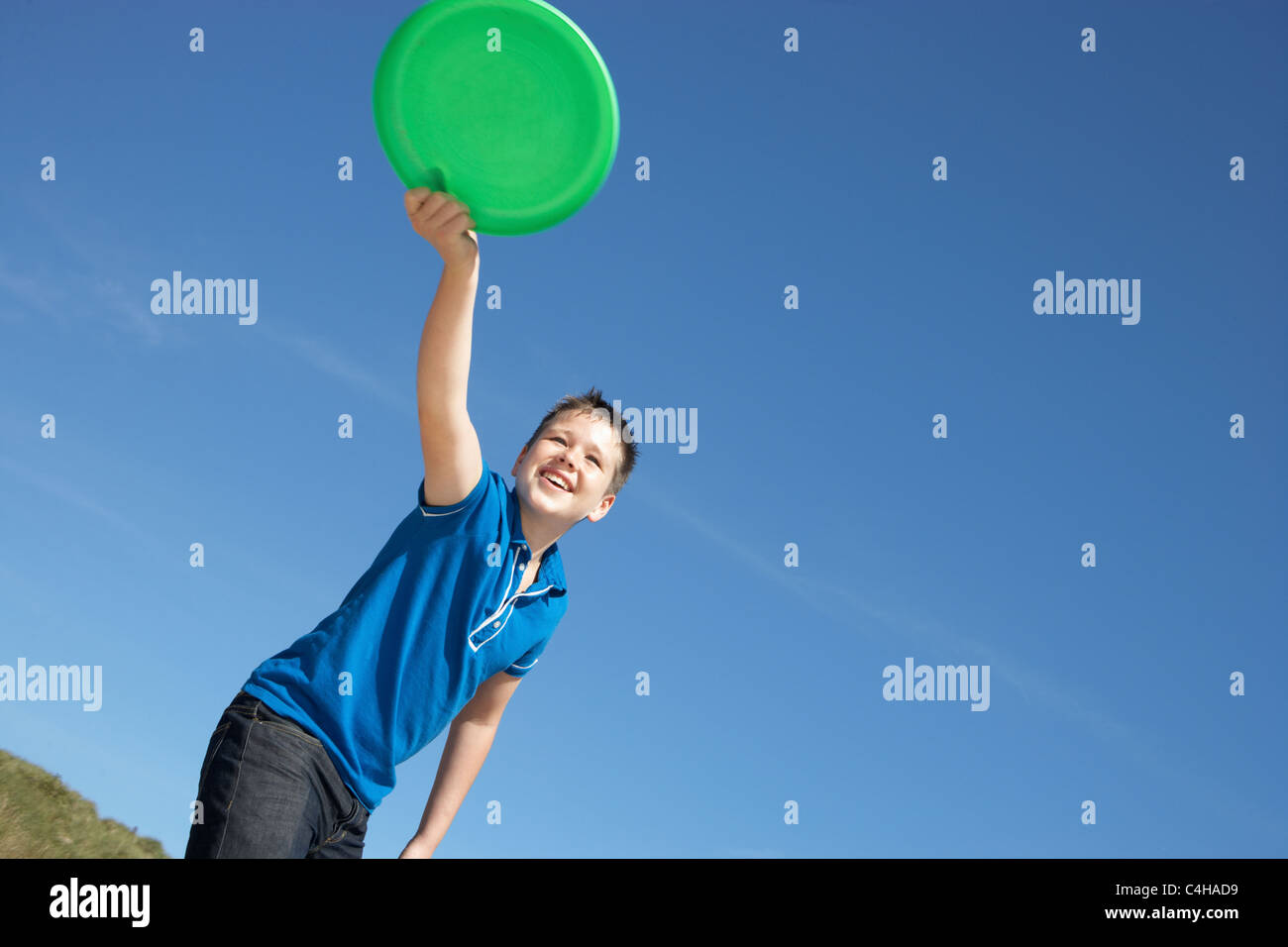 Boy playing frisbee on beach - Stock Image