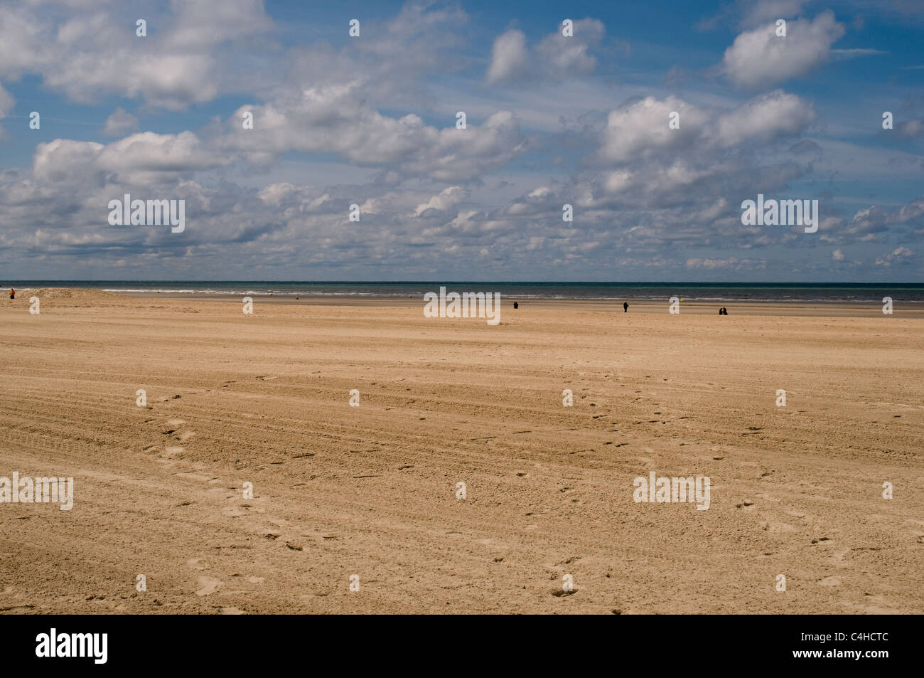 White fluffy clouds float in the sky over the deserted wide sandy beach at Le Touquet, France - Stock Image