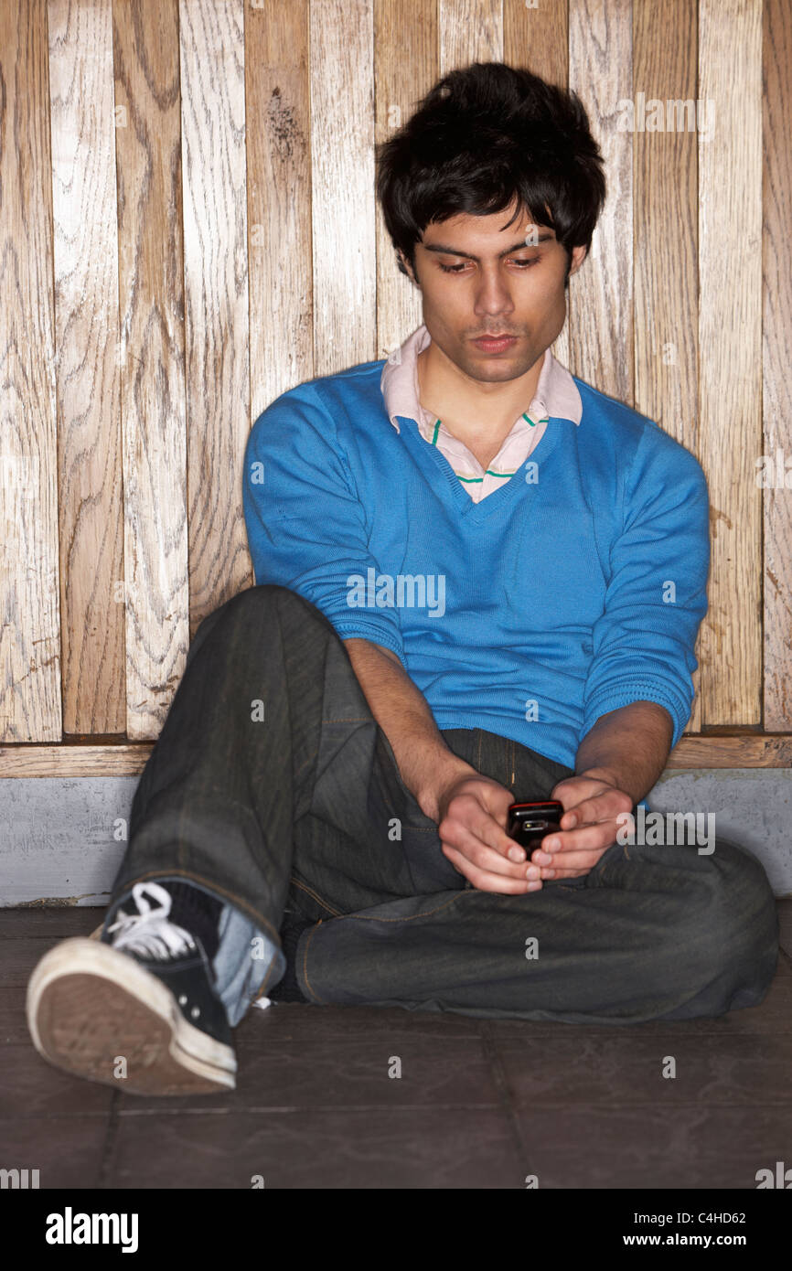 Young man sitting on floor with mobile phone Stock Photo