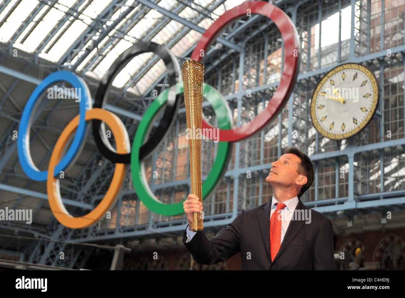 Sebastian Coe (Chairman of LOCOG) looks up at the torch as he holds it under the Olympic rings. 2012 London Olympic - Stock Image