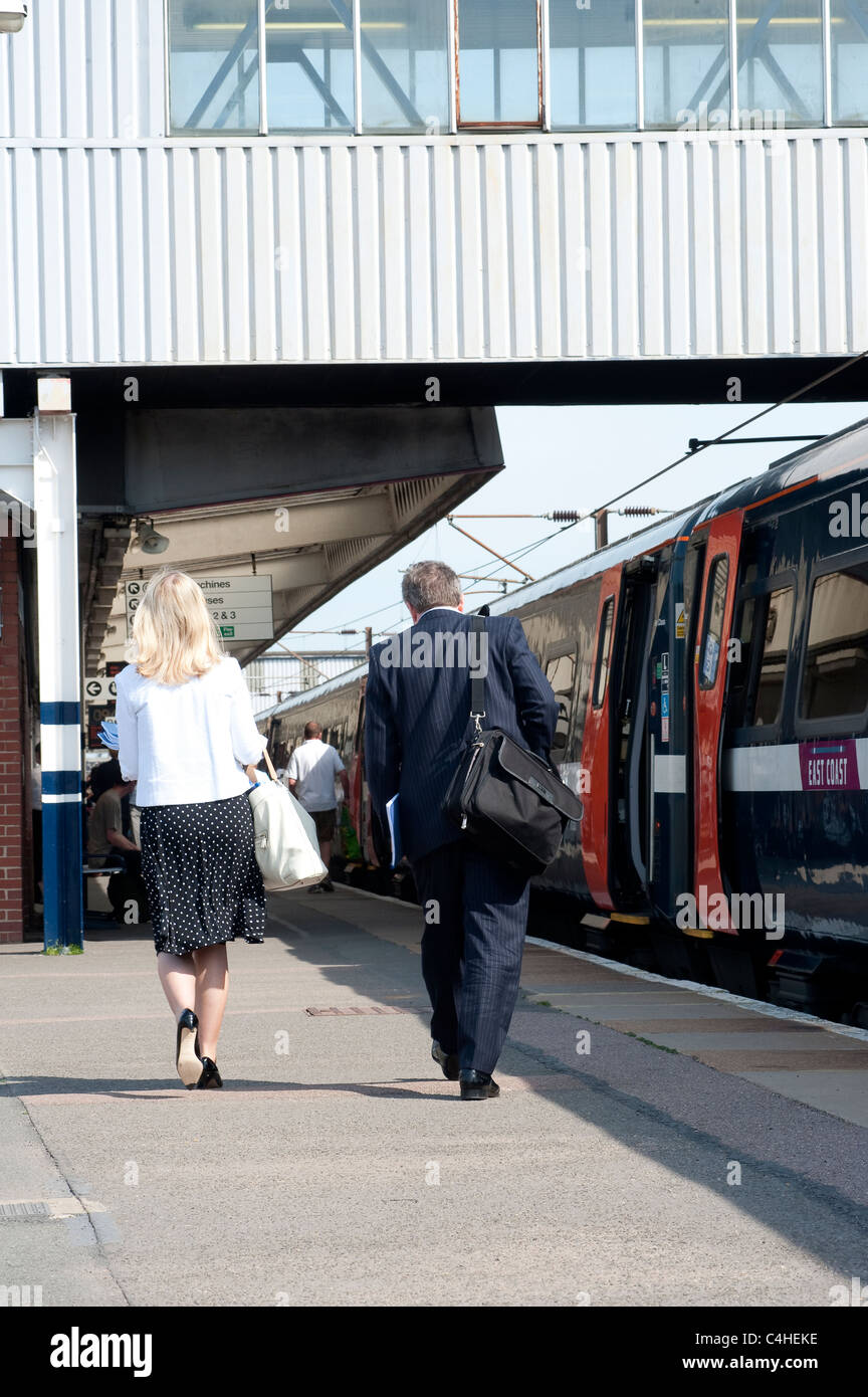 Passengers and train at a railway station in England - Stock Image