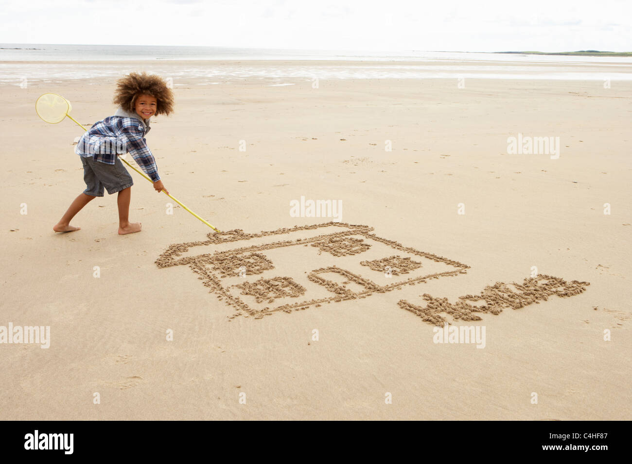 Boy drawing in sand - Stock Image