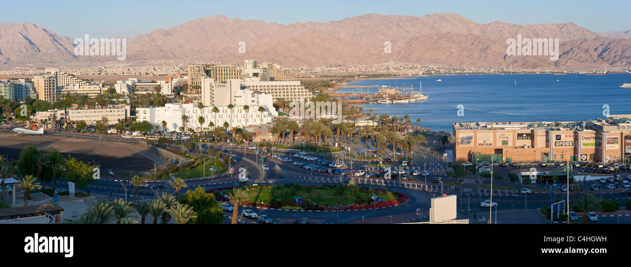 A 3 picture stitch panoramic view of the hotel and beach area of Eilat at sunset with Aqaba in the background. Stock Photo