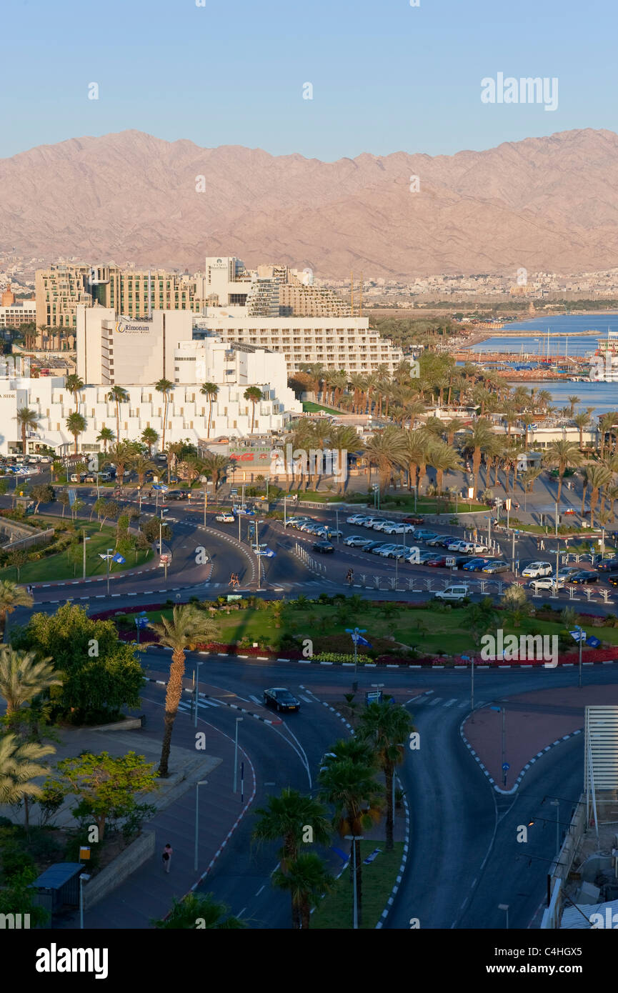A vertical view of the hotel and beach area of Eilat at sunset with the city and coastline of Aqaba in the background. Stock Photo