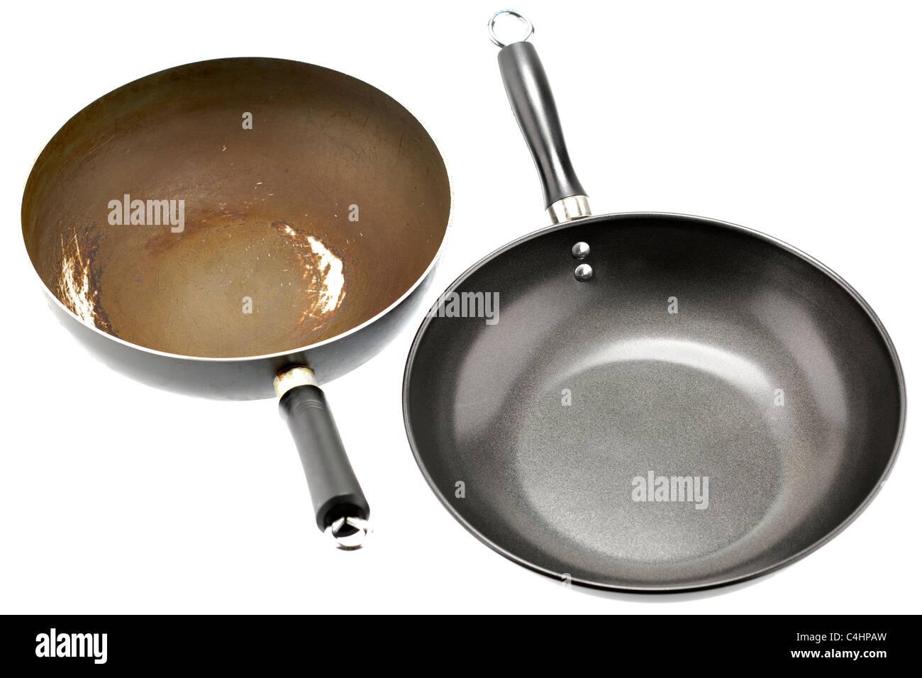 Old and new teflon coated woks. - Stock Image
