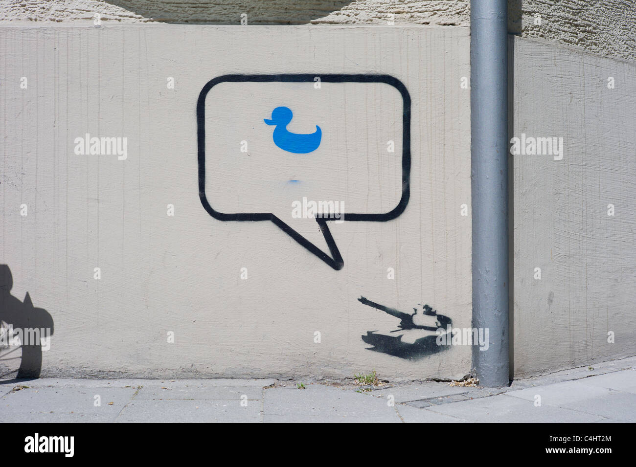 Stencil / graffito on a wall showing a  tank, a speech bubble next to the gun and a blue duck located inside the - Stock Image