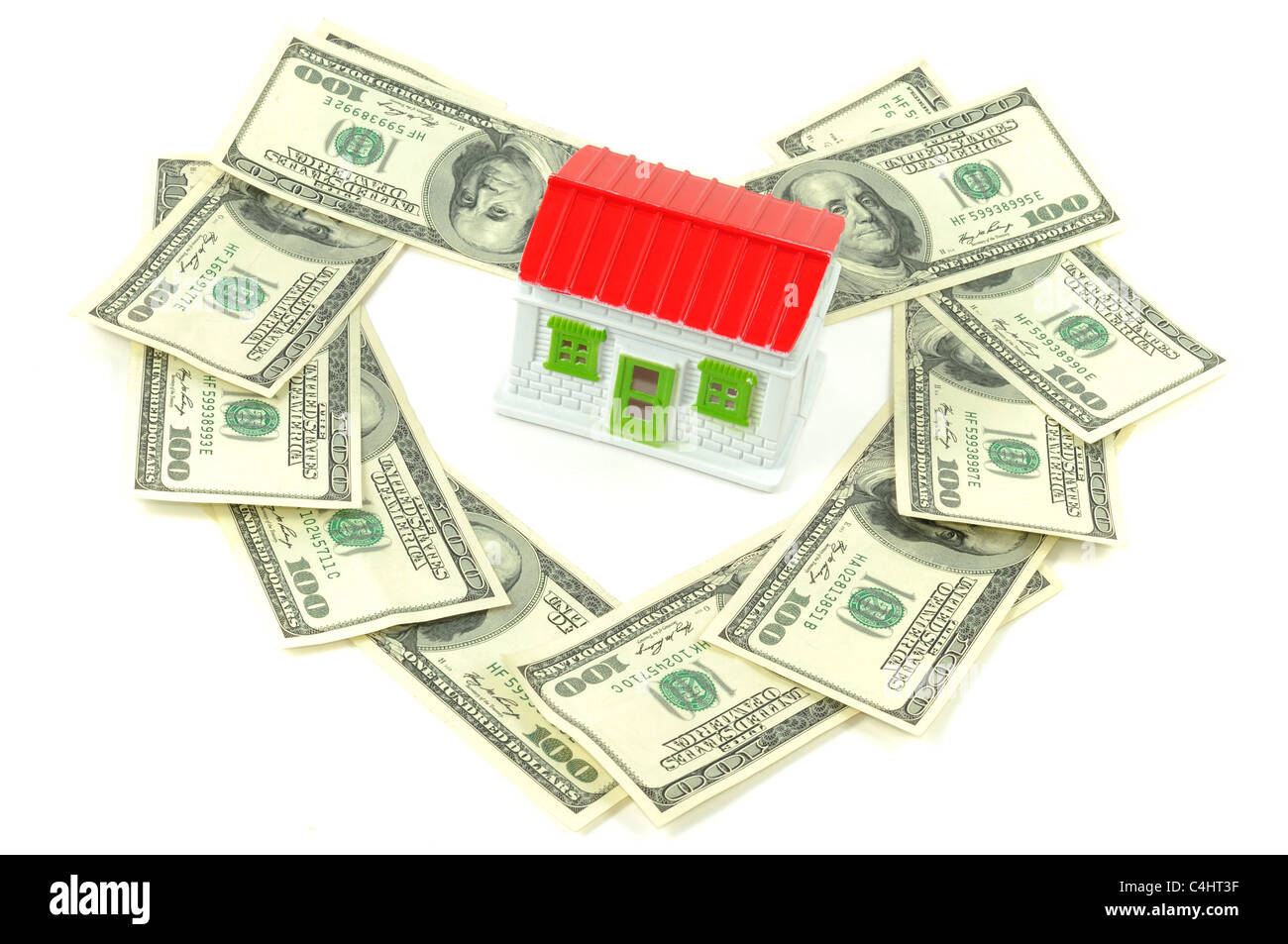 Toy house with hundreds dollars around it, over white background - Stock Image