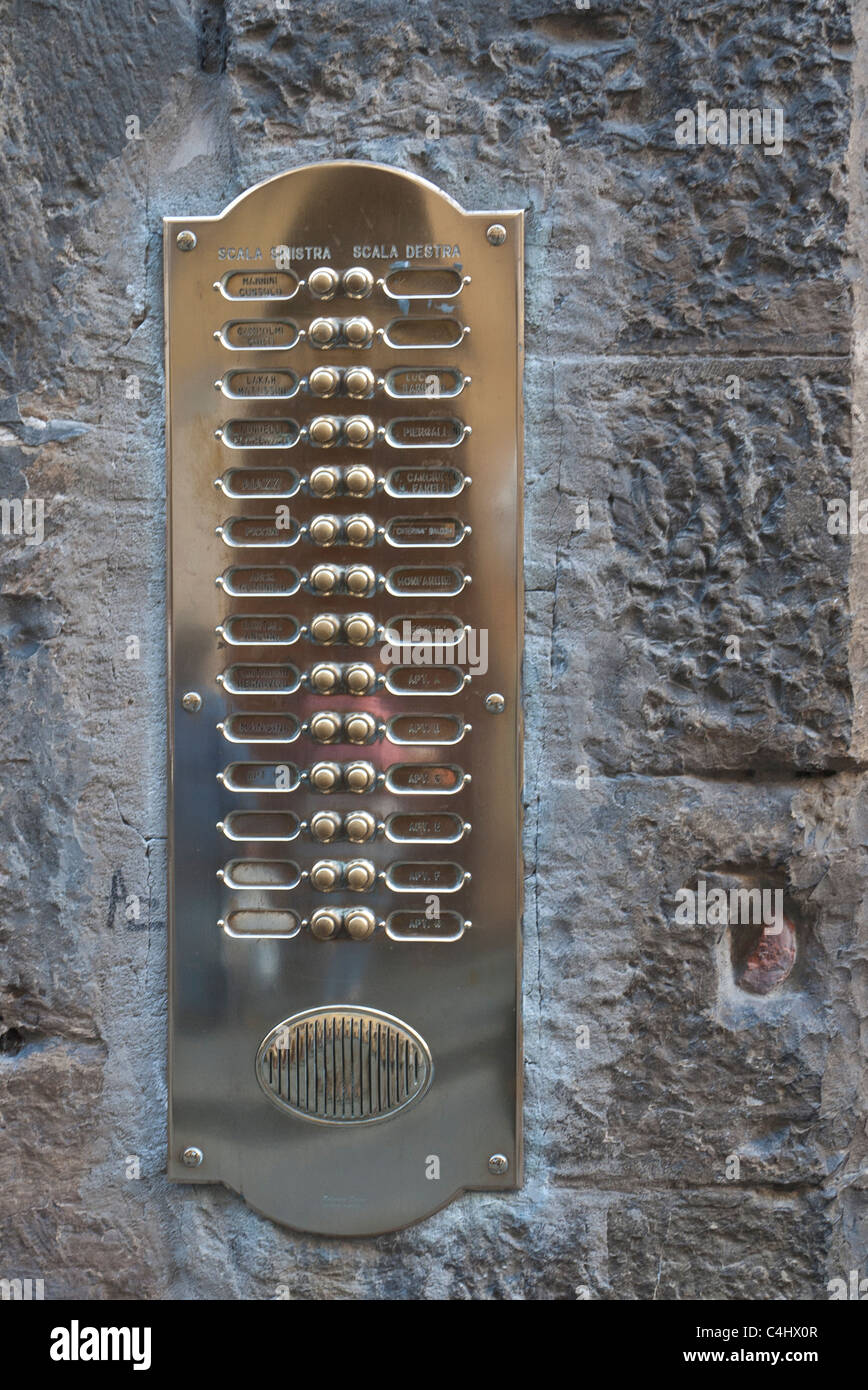 A polished brass plate with doorbells for building residents is embedded in a stone wall of a building in Florence, - Stock Image