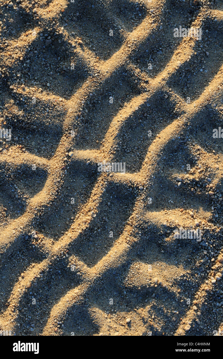 close up of tire tracks on a sandy gravel road - Stock Image