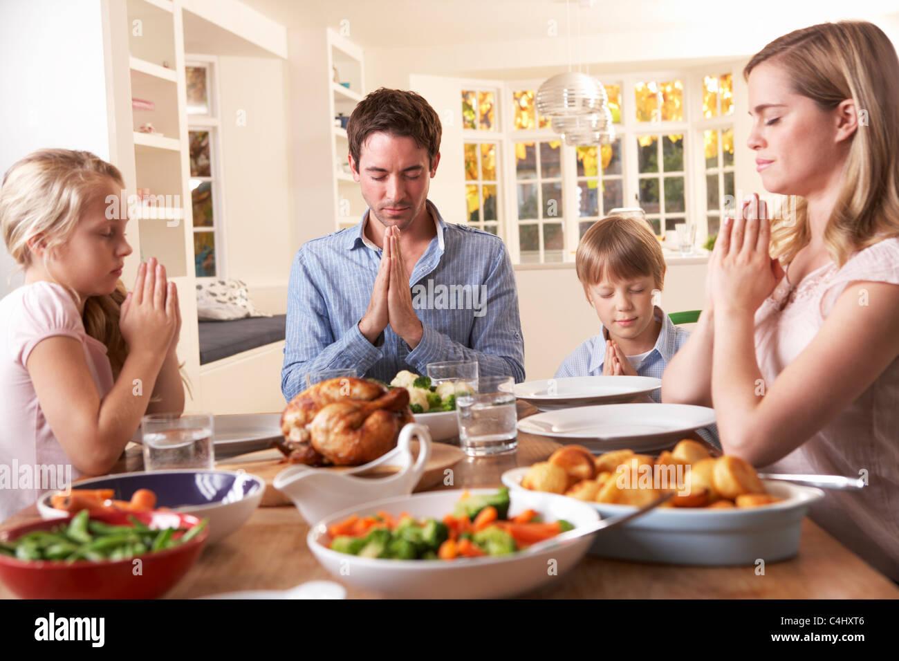 family praying at dinner - 900×600