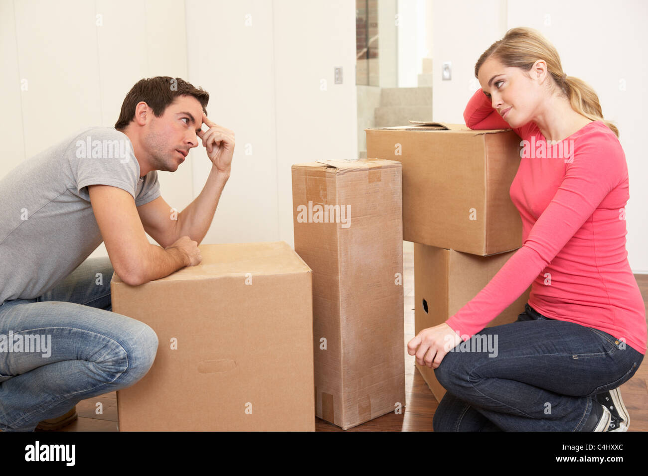 Young couple looking upset among boxes - Stock Image