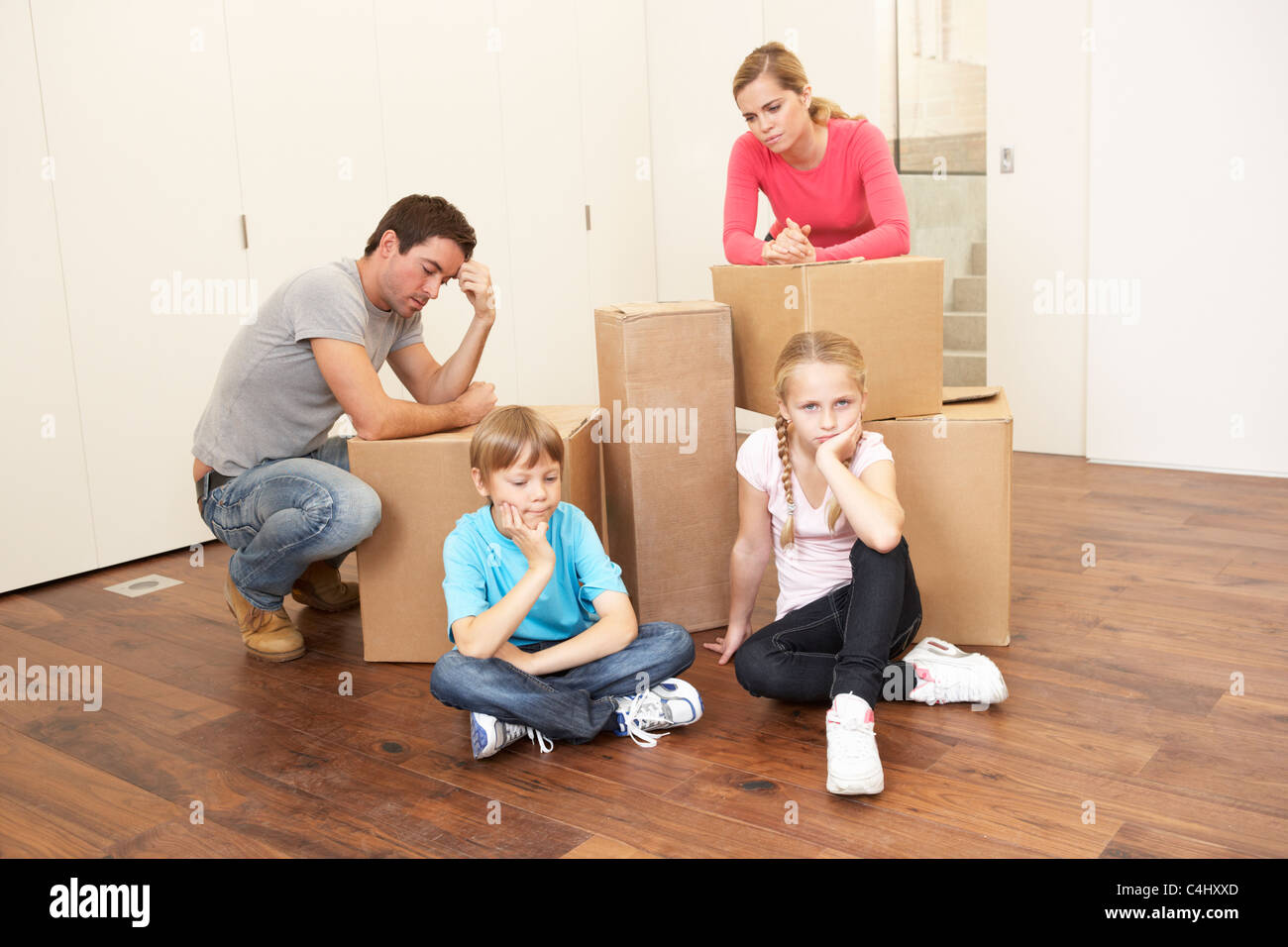 Young family looking upset among boxes - Stock Image