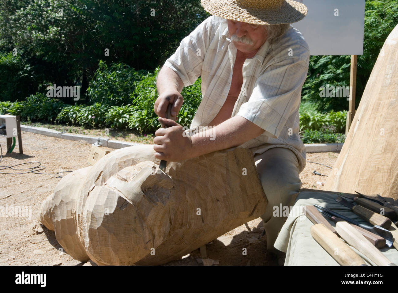 A sculptor creates a wooden sculpture - Stock Image