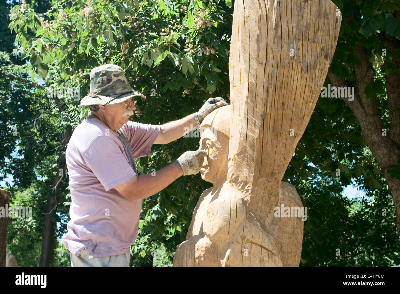 A sculptor creates a wooden sculpture - Stock Image