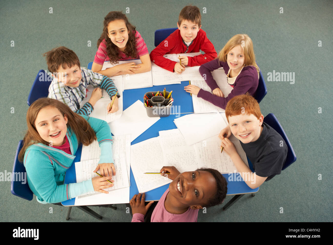 Overhead View Of Schoolchildren Working Together At Desk - Stock Image