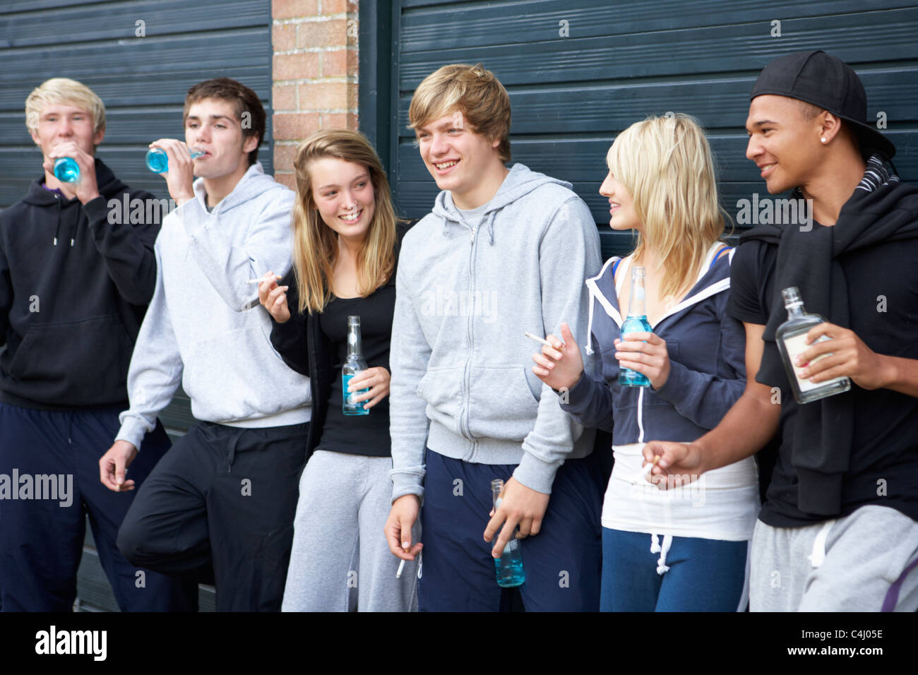 Group Of Teenagers Hanging Out Together Outside Drinking - Stock Image
