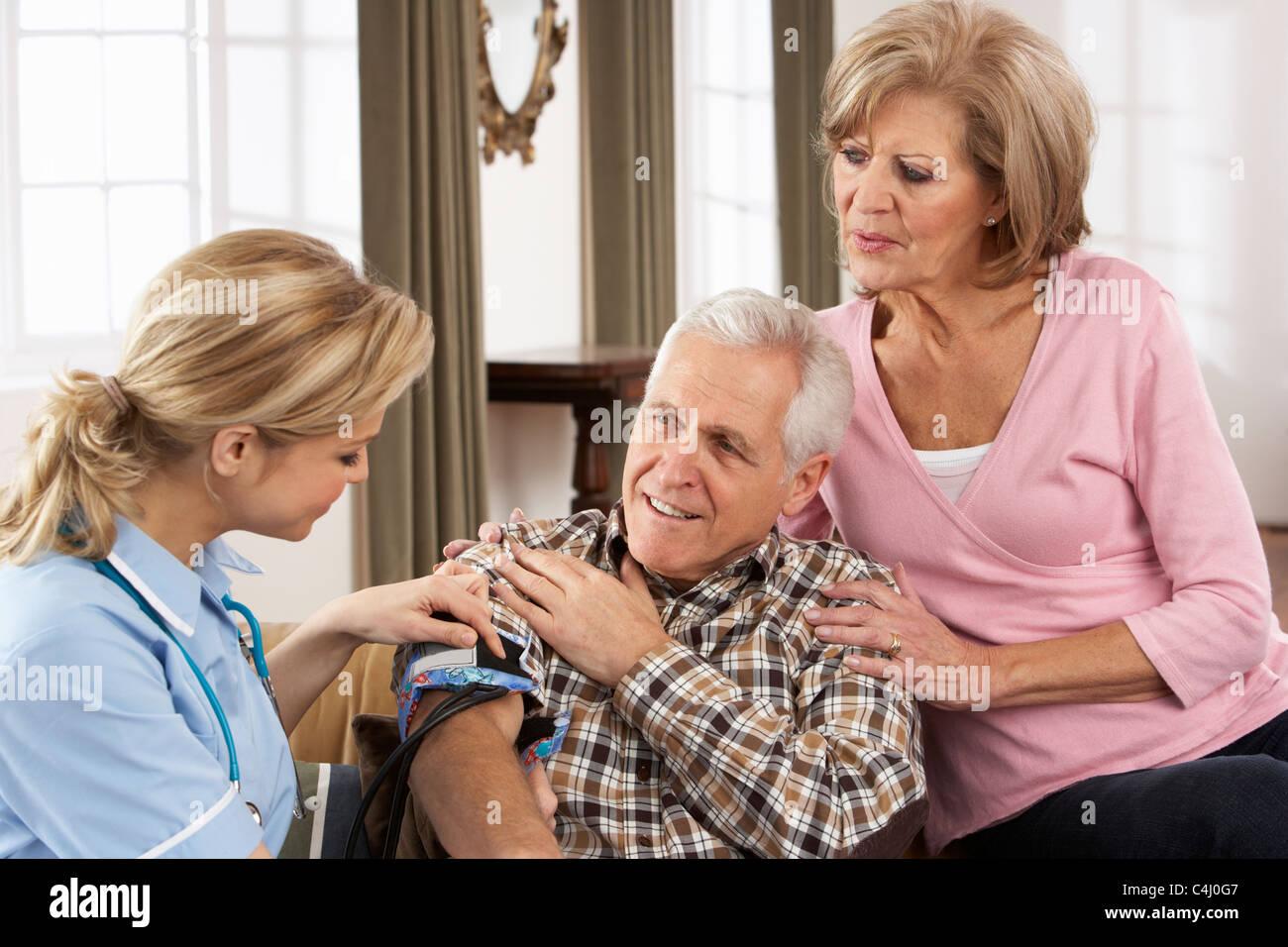 Health Visitor Taking Senior Man's Blood Pressure - Stock Image