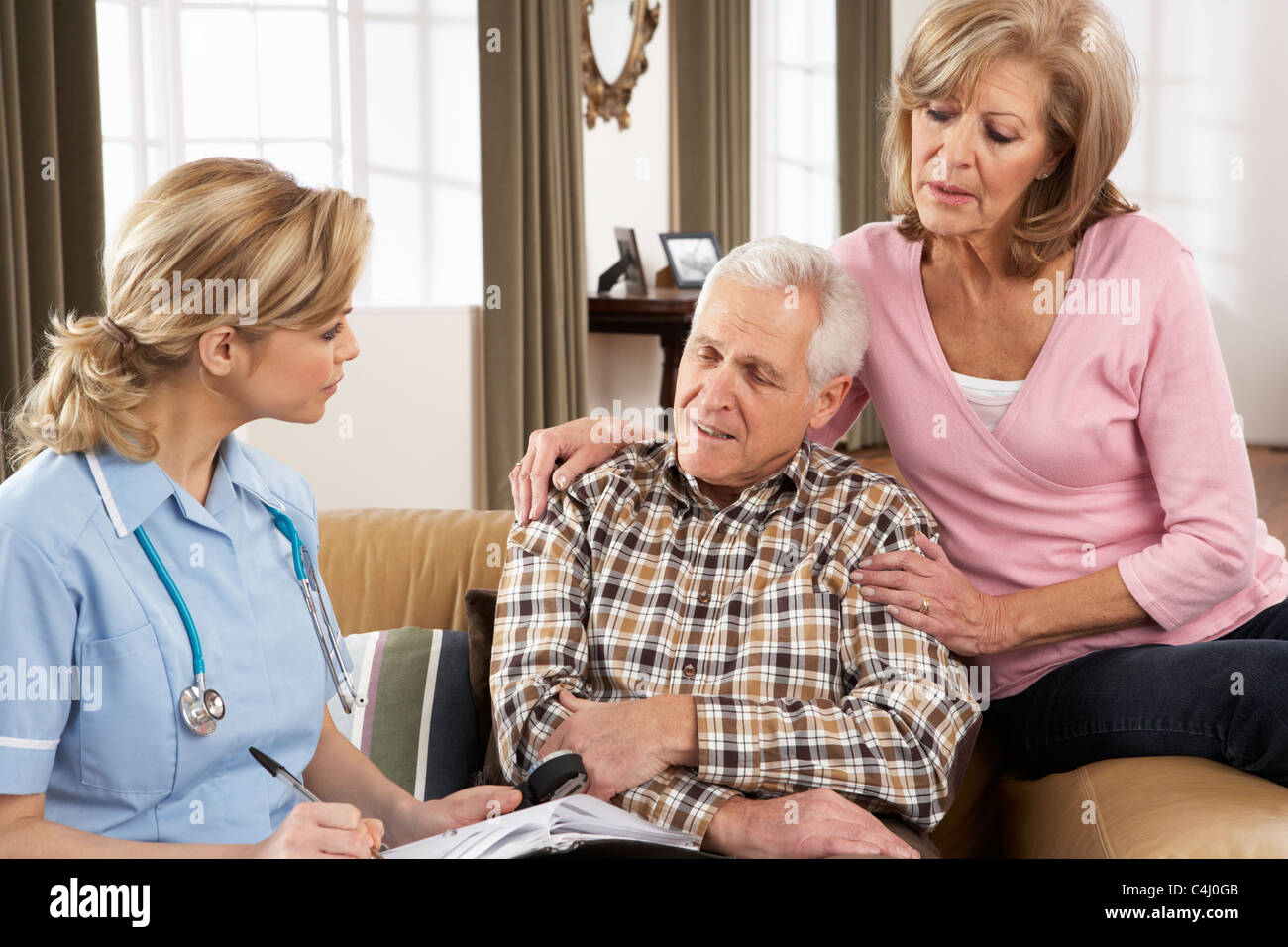 Senior Couple Talking To Health Visitor At Home - Stock Image